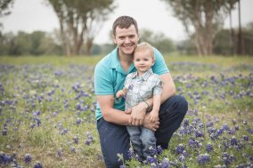boy and dad posing in bluebonnets