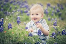 boy sitting in bluebonnets laughing