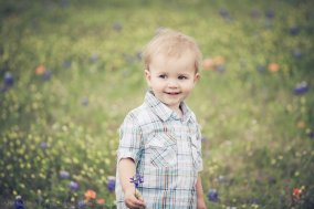 boy smiling picking flowers