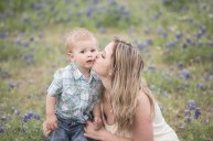 lady kissing son in flowers