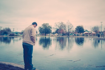 man looking into pond