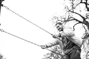 man swinging and smiling