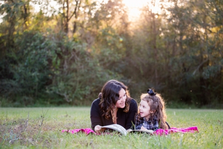 girl and mom reading book in park