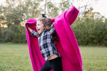girl running with pink blanket