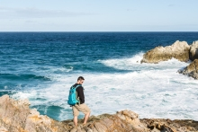 man walking on rocks on stradbroke island