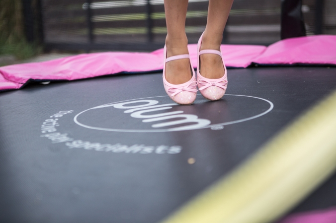 girl in pink shoes on trampoline