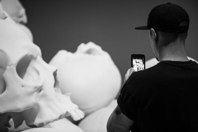 man photographing giant skull