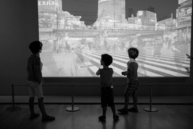 little boys looking at projection of city